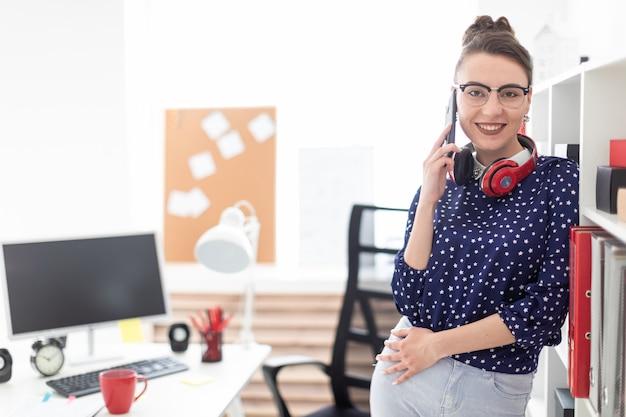 Uma jovem em copos está de pé no escritório perto do rack e falando ao telefone Foto Premium