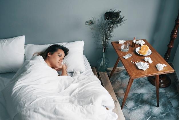 Uma jovem em uma cama doente olha seus remédios com o canto do olho Foto Premium
