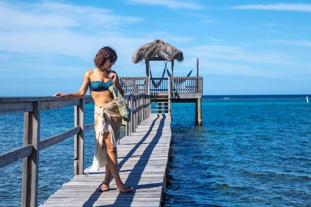 Uma jovem em uma passarela de madeira acima do mar do caribe, na ilha roatan. honduras Foto Premium