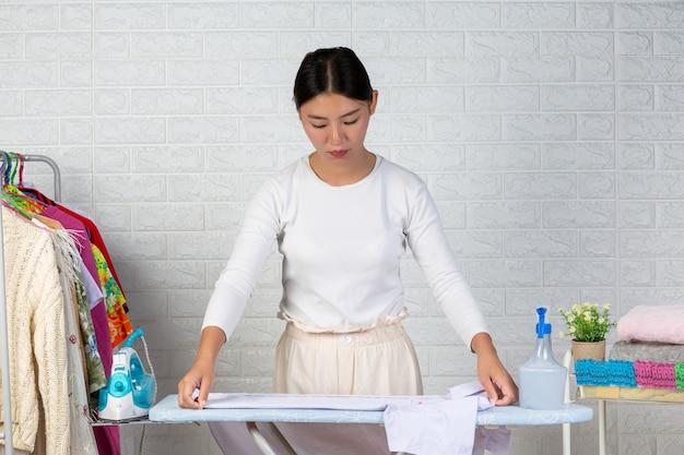 Uma jovem empregada que está preparando uma camisa na tábua de passar roupas com um tijolo branco. Foto gratuita