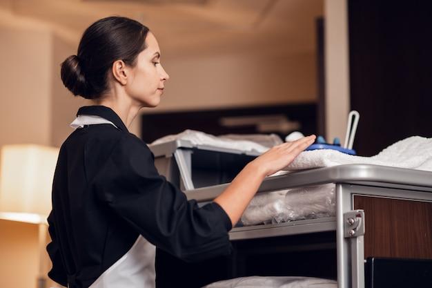 Uma jovem empregada uniformizada recebendo algumas toalhas limpas Foto Premium