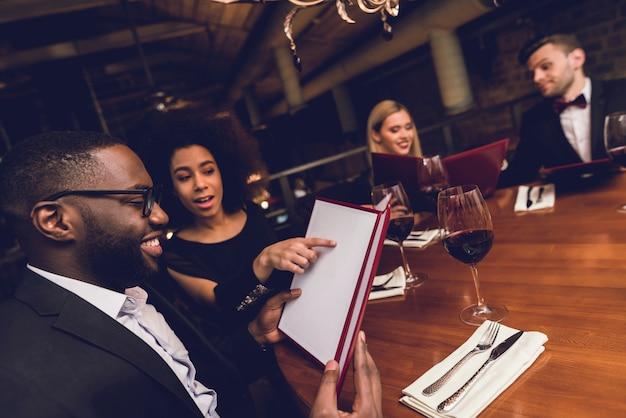 Uma jovem empresa está sentada em um restaurante. Foto Premium