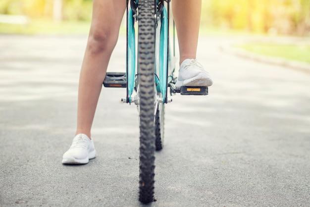 Uma jovem está a andar de bicicleta ao pôr do sol no parque Foto Premium