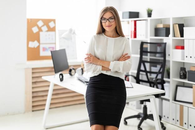 Uma jovem está de pé encostado em uma mesa no escritório. Foto Premium