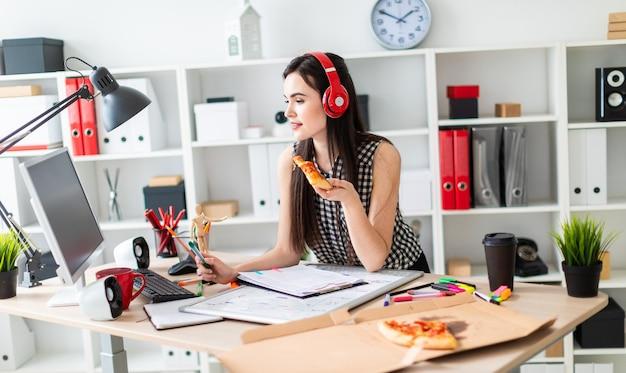 Uma jovem está de pé perto de uma mesa, segurando um marcador verde e um pedaço de pizza na mão antes da menina sobre a mesa é uma placa magnética na cabeça da menina usando fones de ouvido Foto Premium
