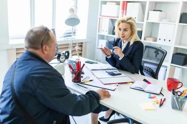 Uma jovem está sentado em uma mesa no escritório, segurando os óculos na mão e falar com um homem Foto Premium