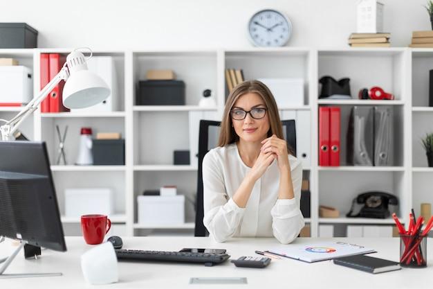 Uma jovem está sentado na mesa do computador no escritório. Foto Premium