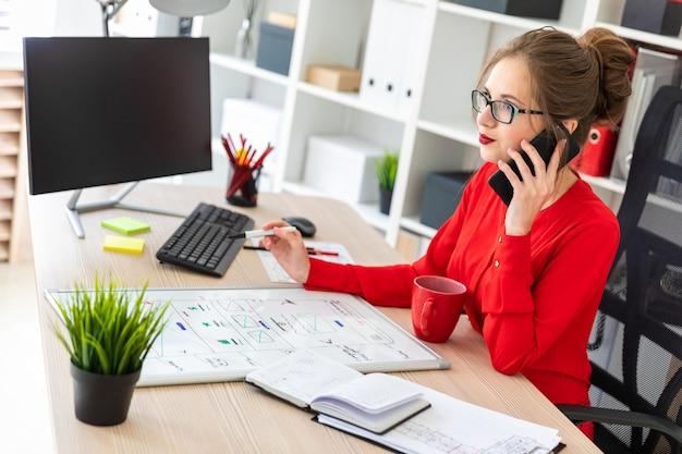 Uma jovem está sentado na mesa do escritório, segurando um marcador na mão Foto Premium