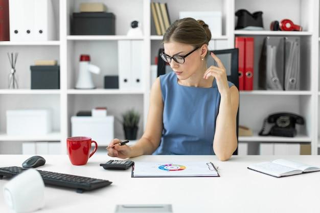 Uma jovem está sentado na mesa do escritório, segurando uma caneta na mão e contando com a calculadora. antes da garota, há uma folha com um diagrama. Foto Premium