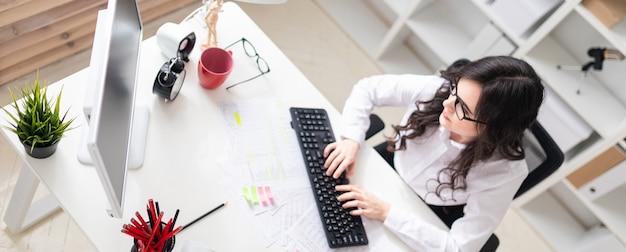 Uma jovem está sentado no escritório no computador e trabalhar com documentos. Foto Premium