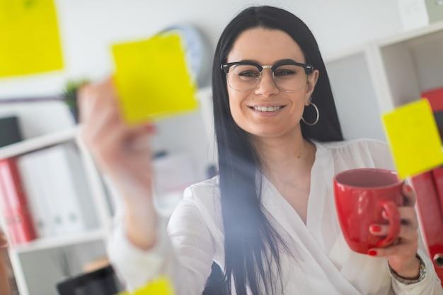 Uma jovem fica perto da placa com adesivos e detém um copo vermelho e lápis nas mãos dela. Foto Premium