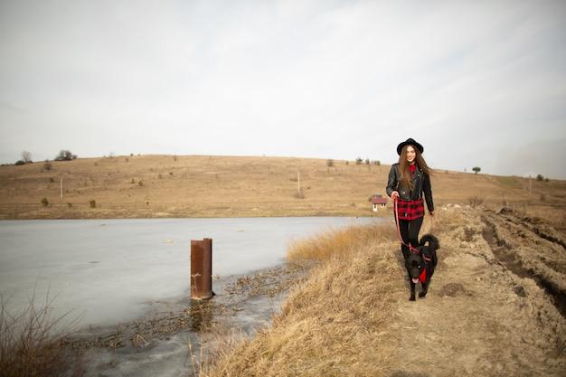 Uma jovem garota anda com um cachorro na margem de um lago Foto Premium
