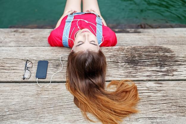 Uma jovem garota coloca em um píer e ouve música em fones de ouvido. Foto Premium