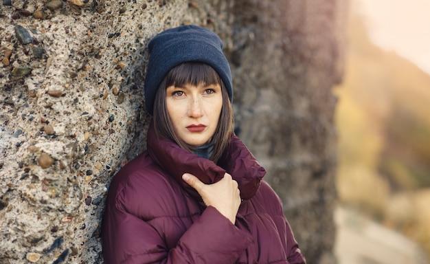Uma jovem garota de chapéu azul e jaqueta misteriosamente desvia o olhar. Foto Premium
