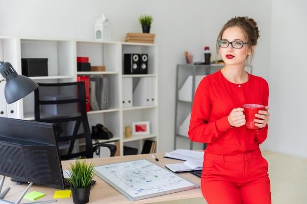 Uma jovem garota está de pé encostado em uma mesa e segurando um copo vermelho nas mãos. Foto Premium