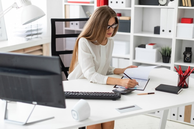 Uma jovem garota está sentada na mesa do computador no escritório, segurando um lápis na mão e fazendo anotações Foto Premium