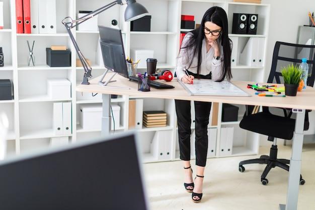Uma jovem garota fica perto de uma mesa de computador e desenha um marcador em uma placa magnética. Foto Premium