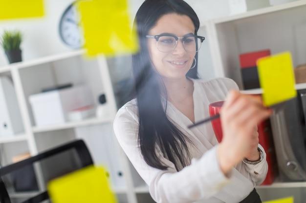 Uma jovem garota fica perto do quadro com adesivos e tem um copo vermelho e lápis nas mãos dela. Foto Premium