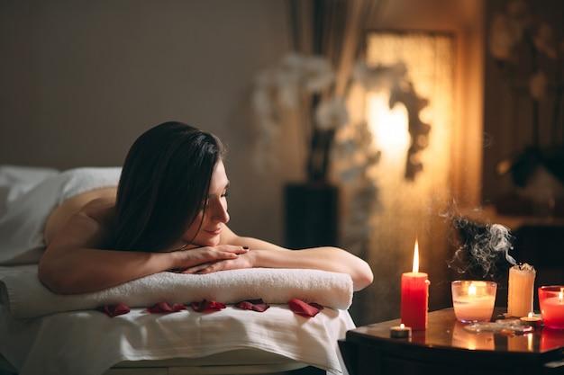 Uma jovem garota linda de cabelos escuros está esperando por uma massagem. Foto Premium