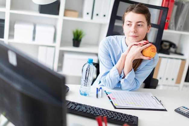 Uma jovem garota se senta em uma mesa no escritório e tem uma maçã na mão. Foto Premium