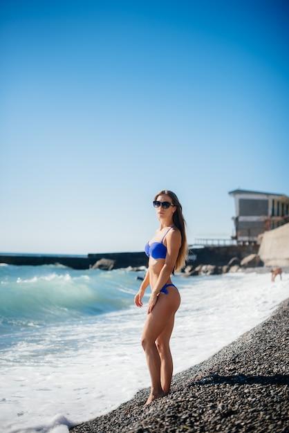 Uma jovem garota sexy está descansando no oceano em um dia ensolarado. recreação, turismo Foto Premium