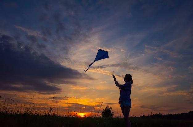 Uma jovem lança uma pipa no céu. silhueta contra o pôr do sol Foto Premium