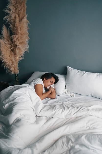 Uma jovem latina assoando o nariz com um lenço de papel enquanto está na cama Foto Premium
