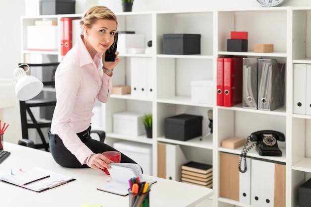 Uma jovem loira senta-se sobre a mesa no escritório, fala ao telefone e folheia o bloco de notas. Foto Premium