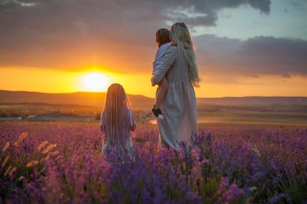 Uma jovem mãe com dois filhos, olhando para o sol de saída em um campo de lavanda Foto Premium