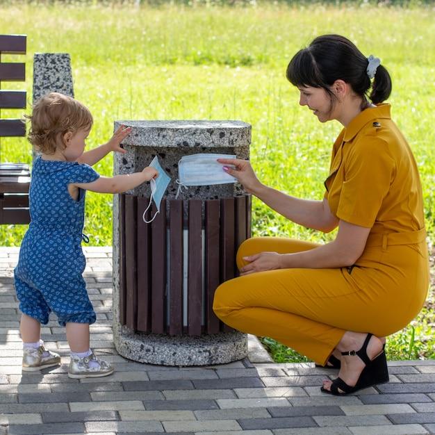 Uma jovem mãe com uma filha pequena joga máscaras médicas no lixo em um dia ensolarado de verão, o conceito de acabar com a pandemia do coronavírus Foto Premium