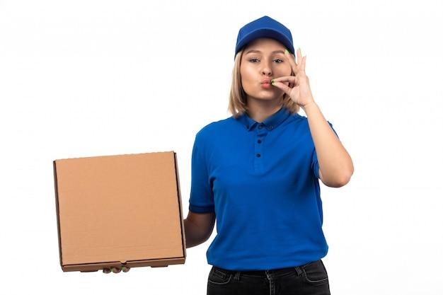 Uma jovem mensageira de uniforme azul segurando um pacote de entrega de comida Foto gratuita