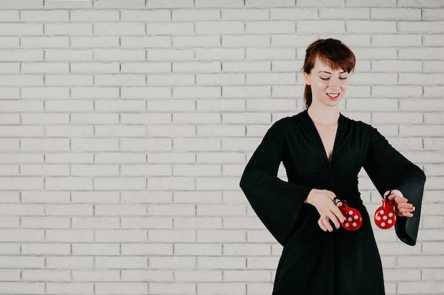Uma jovem mulher atraente de vestido preto, dançando com castanholas vermelhas, sorrindo, fundo de parede branca Foto Premium