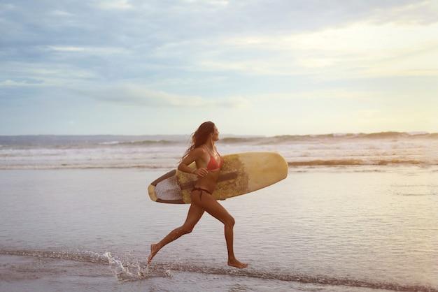 Uma jovem mulher com surf branco nas mãos correndo ao longo da costa do oceano ao pôr do sol. Foto Premium