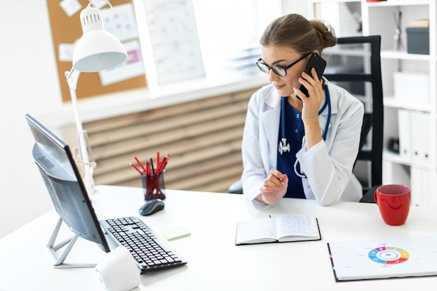 Uma jovem mulher com uma túnica branca está sentada na mesa do escritório, falando ao telefone e segurando uma caneta na mão. um estetoscópio está pendurado no pescoço. Foto Premium