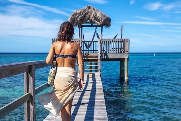 Uma jovem mulher de biquíni caminhando para uma construção de madeira no mar do caribe, na ilha de roatan. honduras Foto Premium