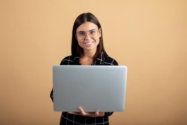 Uma jovem mulher em um vestido xadrez fica em uma laranja com um laptop Foto Premium