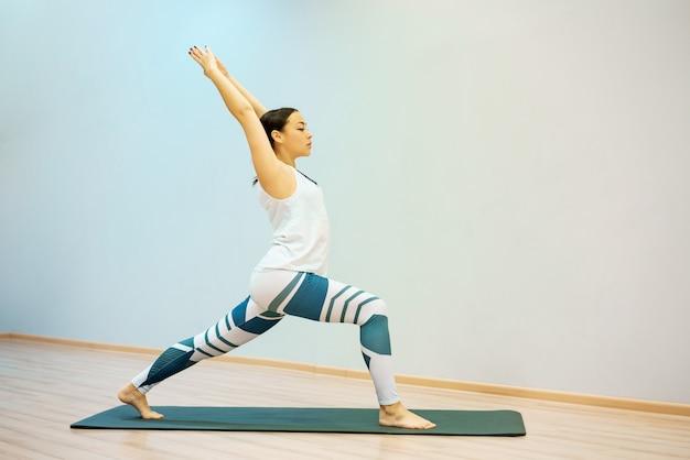 Uma jovem mulher está envolvida em fitness em casa no tapete Foto Premium