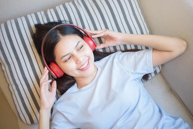 Uma jovem mulher está usando fone de ouvido desfrutando com música na sala de estar Foto Premium