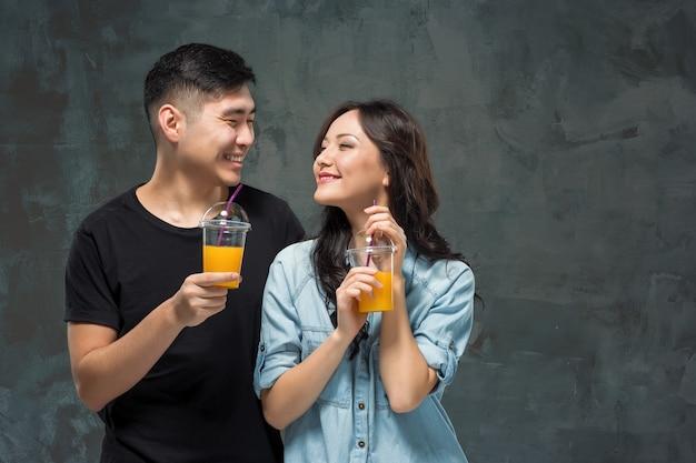 Uma jovem mulher muito asiática com um copo de suco de laranja nas mãos no fundo cinza do estúdio. Foto gratuita