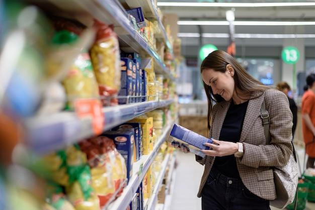 Uma jovem mulher na loja lê o rótulo de macarrão na embalagem Foto Premium
