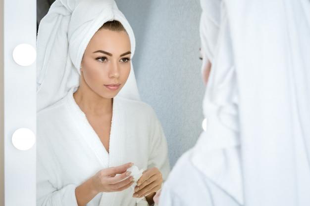 Uma jovem mulher olha no espelho com uma toalha na cabeça, segurando um creme para o rosto. conceito de cuidados com a pele em hom Foto Premium