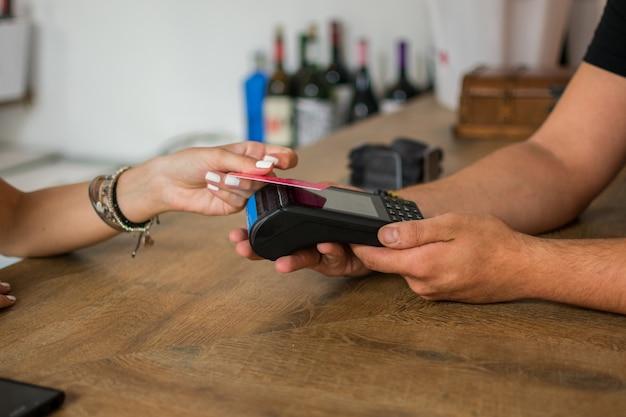 Uma jovem mulher paga com cartão de crédito em um pub. Foto Premium