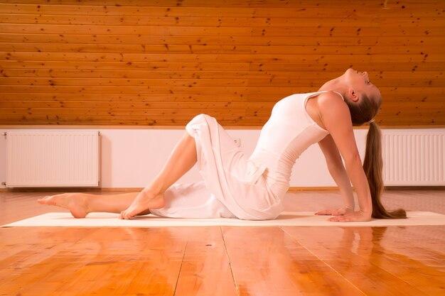 Uma jovem mulher praticando ioga em um estúdio no sótão. Foto Premium