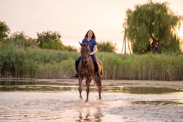 Uma jovem mulher que monta um cavalo em um lago raso. um cavalo corre na água ao pôr do sol. cuide e ande com o cavalo. força e beleza Foto Premium