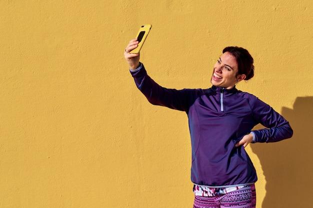 Uma jovem mulher usando seu telefone celular enquanto fazia fitness ao ar livre - conceito de estilo de vida Foto Premium