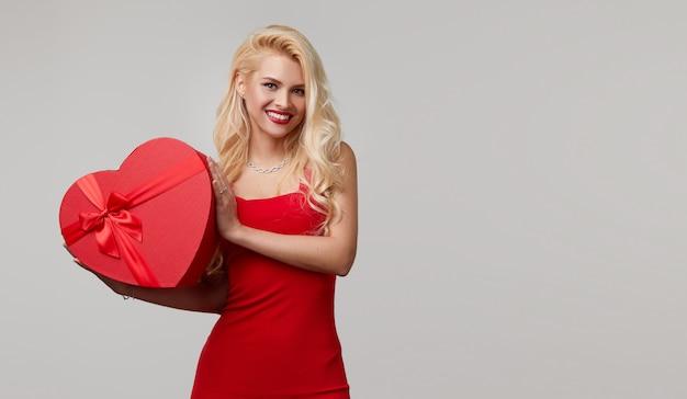 Uma jovem mulher vestida de vermelho manda um beijo. segura nas mãos uma caixa de presente em forma de coração. dia dos namorados e 8 de março Foto Premium