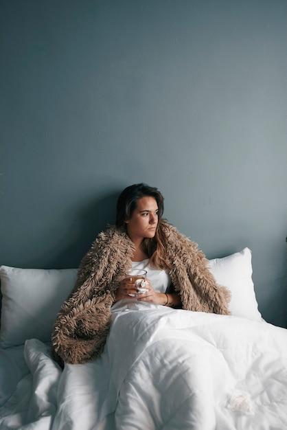 Uma jovem na cama com um cobertor está bebendo chá quente Foto Premium