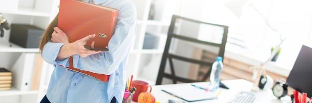 Uma jovem no escritório está de pé, inclinando-se sobre uma mesa e está segurando um telefone e uma pasta com documentos. Foto Premium