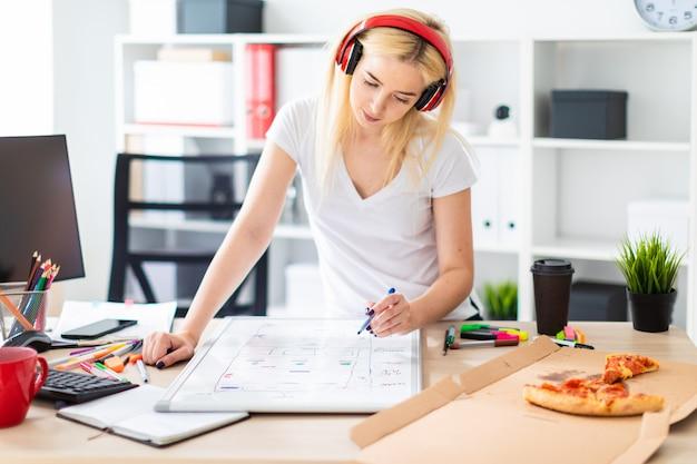 Uma jovem nos fones de ouvido fica perto da mesa e detém um marcador na mão sobre a mesa é um quadro magnético Foto Premium