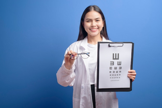 Uma jovem oftalmologista com óculos segurando um gráfico sobre a parede azul, conceito de saúde Foto Premium
